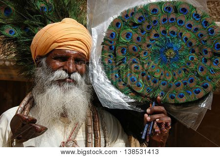 Jaisalmer, India - march 12, 2006: Souvenir salesman shows some fans made with peacock feathers, yin the streets of Jaisalmer