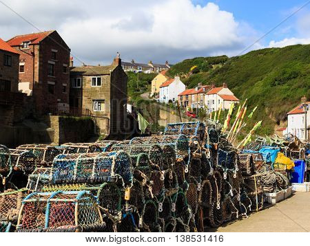 STAITHES ENGLAND - JULY 12: Lobster pots stacked on the quayside. In Staithes North Yorkshire England. On 12th July 2016.