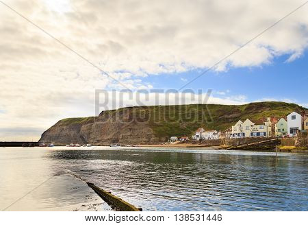 STAITHES ENGLAND - JULY 12: The harbour and seafront cliffs beyond. In Staithes North Yorkshire England. On 12th July 2016.