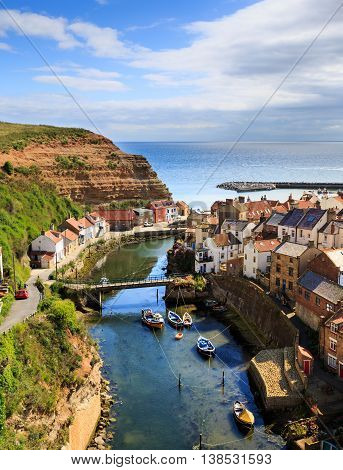 STAITHES ENGLAND - JULY 12: The classic view of Staithes from a high viewpoint showing the beck and the town. In Staithes North Yorkshire England. On 12th July 2016.