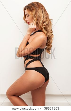 sexy girl with beautiful curly hair standing in a swimsuit near the white wall
