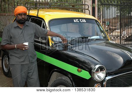 New Delhi, India - february 21, 2006: Sikh cab driver with his car in a taxi station