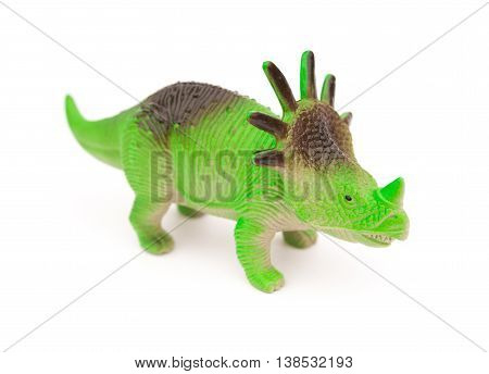 green styracosaurus toy on a white background