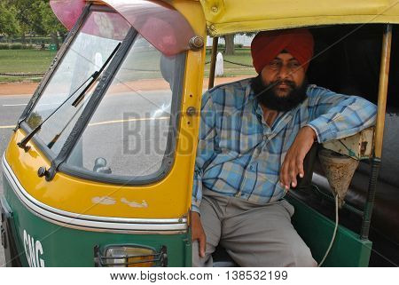 New Delhi - march 20, 2006: Sikh driver, sitting inside a motorbike taxi in the city of New Delhi