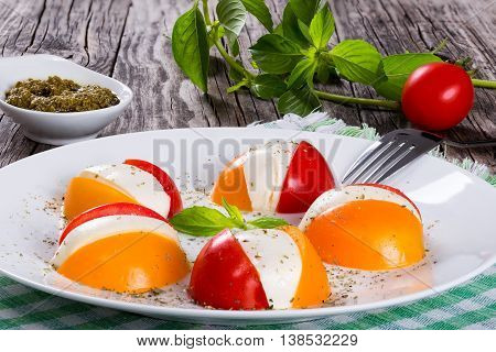 red and yellow tomatoes and mozzarella caprese salad on white dish sprinkled with dried herbs sauce pesto and basil bunch on background italian style close-up