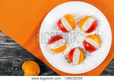 delicious tomato. mozzarella basil caprese summer salad on white dish on orange table mat with half of yellow tomato on background view from above