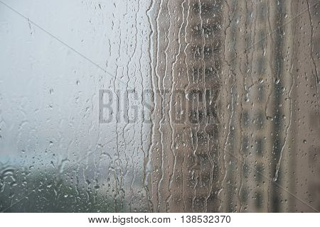 rain drops on glass with a residential building on background