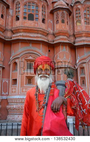 Jaipur, India - february 22, 2006: An ascetic with red dress near the Palace of the Winds , Hawa Mahal