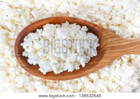 crumbly cottage cheese in the wooden spoon lying on the cottage cheese