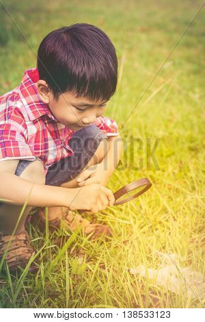 Young Boy Exploring Nature With Magnifying Glass. Outdoors In The Day Time. Warm Tone