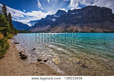 The waters of lake surrounded by  Canadian Rocky Mountains. Azure Bow Lake in Banff National Park
