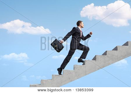 Image of confident businessman with briefcase walking upstairs