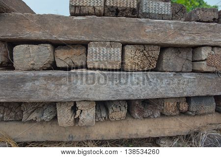 Many old railway sleepers stacked in the outdoors.