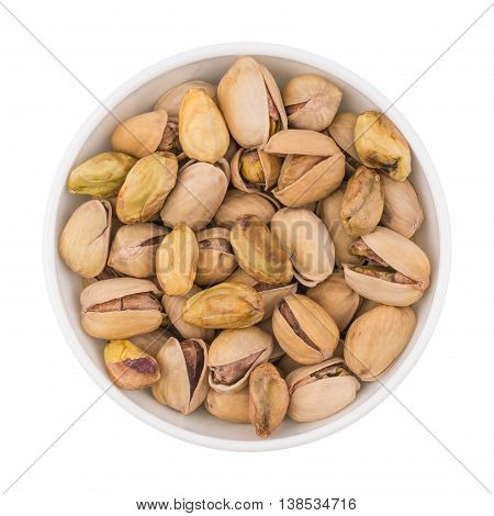 At the center of the frame white bowl with pistachio nuts on a white background. Salted roasted pistachios. Close. Horizontal shot. Top view.