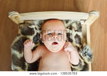 sweet newborn baby lying on the little bed