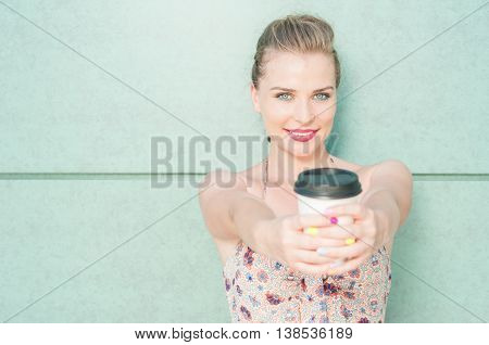 Beautiful Woman Offering Takeaway Coffee Cup And Smiling