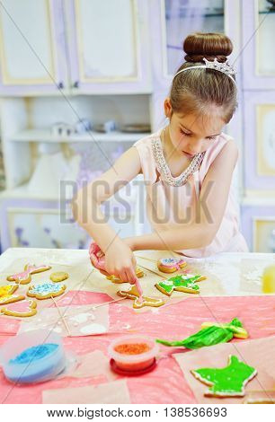 birthday girl decorating cookies at birthday party