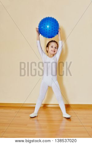 little girl wearing white leotard with ball
