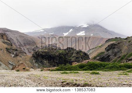 Icelandic landscape with red hills and black rocks in Lonsoraefi