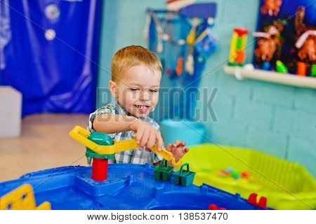 happy little boy is playing water toy