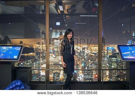 CHICAGO, IL - CIRCA MARCH, 2016: indoor portrait of woman at John Hancock Center's observatory. The John Hancock Center is a supertall skyscraper at 875 North Michigan Avenue, Chicago.
