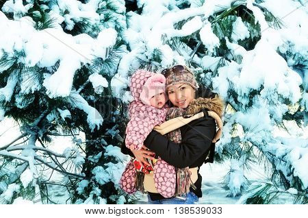 mother with her baby in snow forest