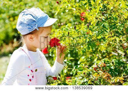 Little Girl  Smelling Rose