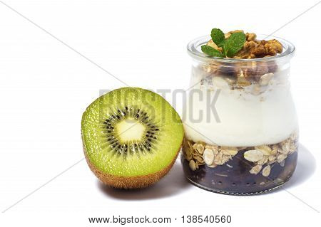 One portion a healthy breakfast - yogurt with dried fruits kiwi honey and nuts and muesli served in glass jar isolated on white. Healthy lifestyle.