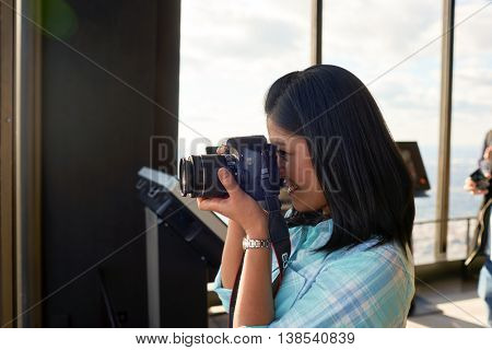 CHICAGO, IL - CIRCA MARCH, 2016: indoor portrait of woman with camera at John Hancock Center's observatory. The John Hancock Center is a supertall skyscraper at 875 North Michigan Avenue, Chicago.