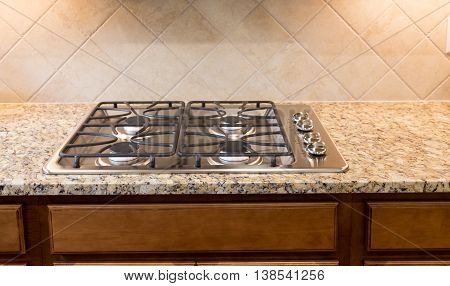 A Stainless Gas Cooktop on Granite Countertop