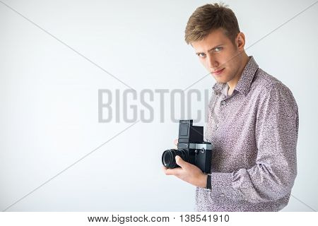 Portrait Of Handsome Man With Old Medium Format Camera In Studio