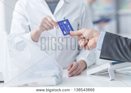 Man at the pharmacy making purchases with a credit card he is giving the card to the female pharmacist hands close up