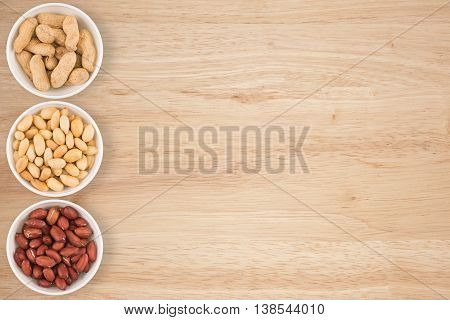 Some peanuts in a cyan bowl on a wooden table.