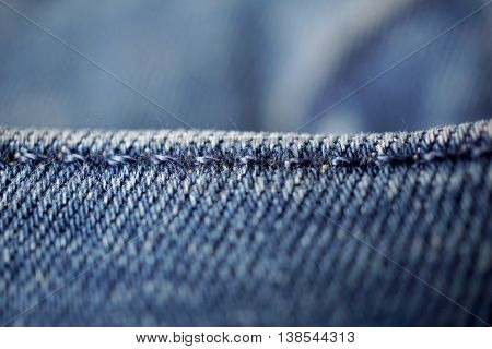Macro detail of a blue thread stitching dark blue stitched pockets of trendy jeans