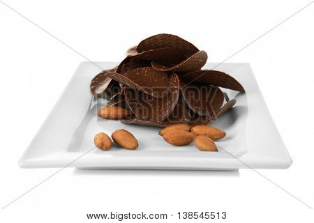 Chocolate chips and almonds in plate on white background