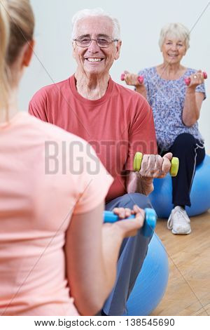 Seniors At Fitness Class With Female Instructor