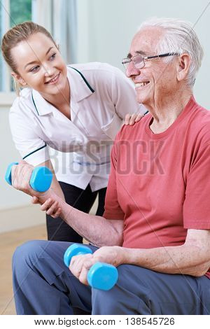 Senior Male Working With Physiotherapist Using Weights