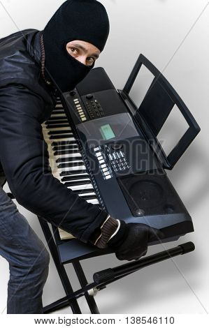 Burglar masked in balaclava is going to steal electronic keyboard.
