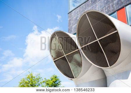 Industrial background of two big modern ventilation pipe tops and blue skies