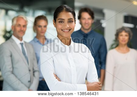 Multiethnic businesswoman standing with her colleagues in background. Portrait of happy smiling busi