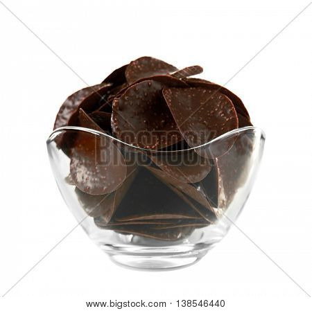 Chocolate chips in glass vase on white background