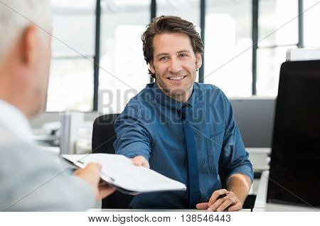 Close up of young businessman giving writing pad to senior businessman. Employees working in an office discussing about future. Businessman handling financial reports to leadership in office.
