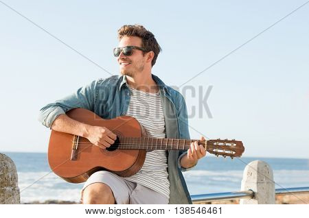 Handsome young man wearing sunglasses and playing guitar on fence near beach. Smiling guy playing ac
