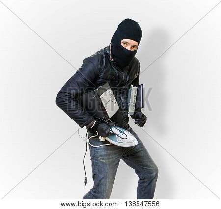 Burglar or thief masked in balaclava is stealing electronics.