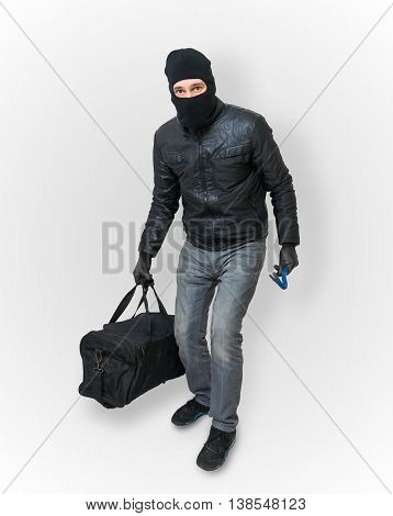 Burglar or thief in balaclava holds crowbar and bag.
