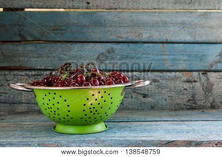 Cherries In A Colander On A Wooden Background
