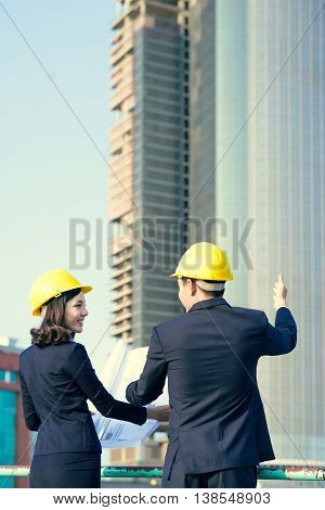Two architects talking to each other . Team of engineers at the construction