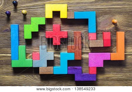 The man in the maze, flat lay. The concept of a business strategy, analytics, search for solutions, the search output. Labyrinth of colorful wooden blocks, tetris, top view.