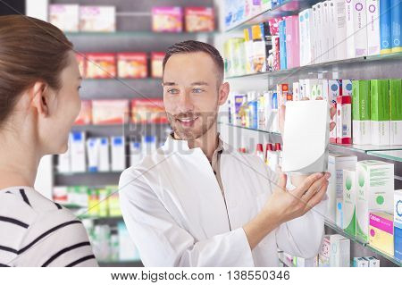 Pharmacist attending customer, showing product with copy space