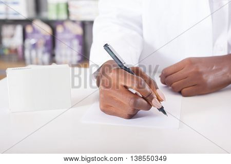 Black pharmacist or doctor writing on tablet package with copy space